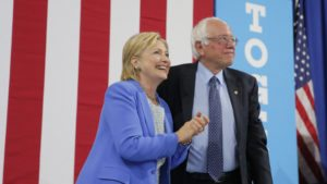 Democratic U.S.  presidential candidate Hillary Clinton and Sen. Bernie Sanders stand together during a campaign rally. Photo: REUTERS/Brian Snyder