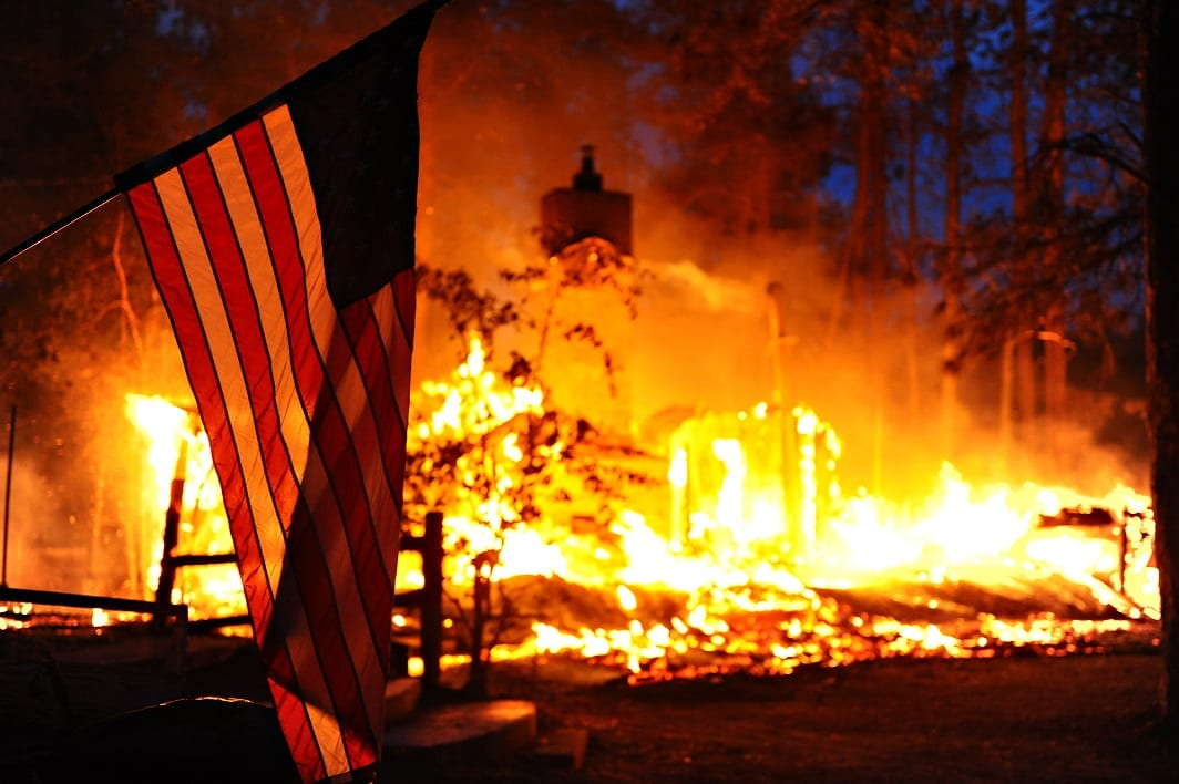 A U.S. flag hangs in front of a burning structure in Black Forest, Colo., June 12, 2013. The structure was among 360 homes that were destroyed in the first two days of the fire, which had spread to 15,000 acres by June 13. The Black Forest Fire started June 11, 2013, northeast of Colorado Springs, Colo., burning scores of homes and forcing large-scale evacuations. The Colorado National Guard and U.S. Air Force Reserve assisted in firefighting efforts. (DoD photo by Master Sgt. Christopher DeWitt, U.S. Air Force/Released)